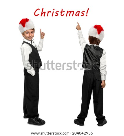 little boy in a tuxedo and  in Santa Claus xmas red hat pointing at wall. Rear view.  - stock photo