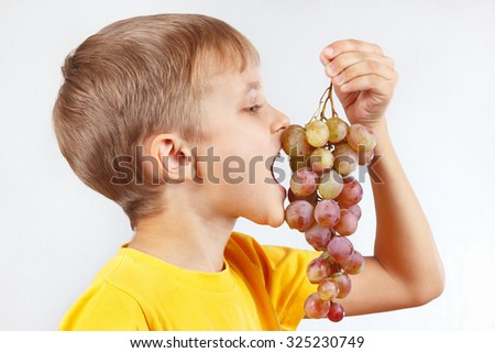 Little boy in a yellow shirt eating a grape - stock photo