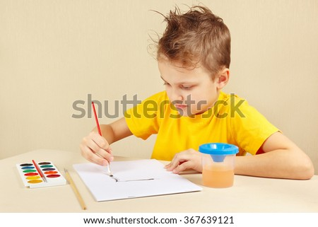 Little boy in a yellow shirt painting colors - stock photo