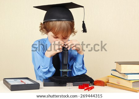 Little boy in academic hat looking through a microscope at his desk - stock photo
