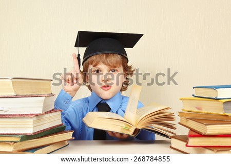 Little boy in academic hat quoted the old book - stock photo