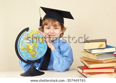 Little boy in academic hat with a globe among the old books - stock photo