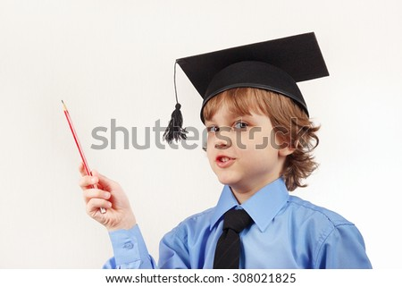 Little boy in academic hat with pencil on a white background - stock photo