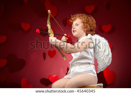Little boy in an image of the cupid on a red background - stock photo
