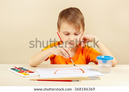 Little boy in an orange shirt painting colors - stock photo