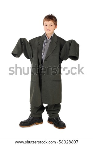little boy in big grey man's suit and boots standing isolated on white background - stock photo