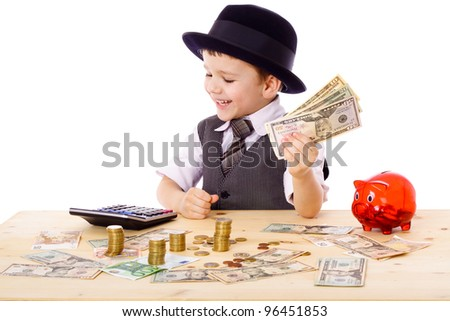 Little boy in black hat and tie at the table counts money, isolated on white - stock photo