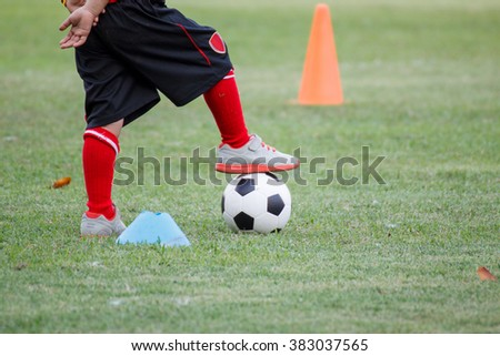 Little boy in black shorts and trainers with his foot on top of a ball on green grass