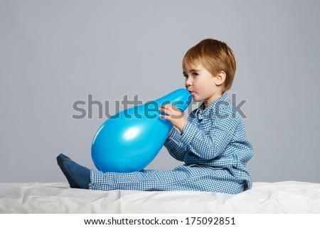 Little boy in blue pyjamas having fun with balloon in bed - stock photo