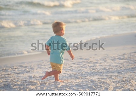 Little boy in blue shirt and yellow shorts running on sand on the beach,  towards setting sun, near ocean waves.