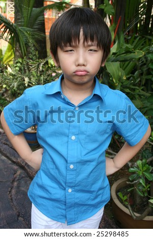 Little boy in blue shirt showing angry face in the park