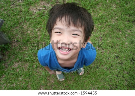 little boy in blue singlet looking up - stock photo