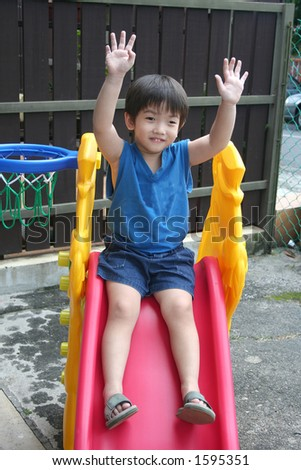 little boy in blue singlet waving both hands on the slide - stock photo