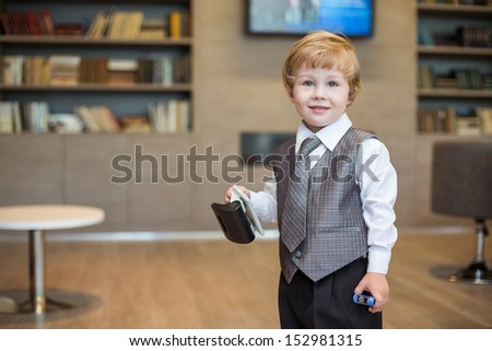 Little boy in business clothes with a puncher and stapler in the business center