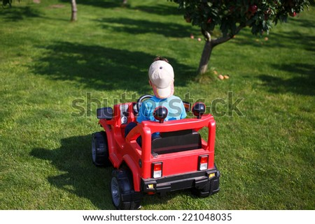 Little boy in cap drive electrical vehicle, outdoor portrait