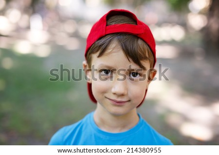 Little boy in cap looking into camera outdoor - stock photo