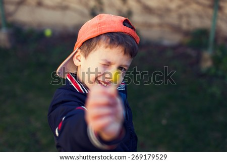 Little boy in cap showing yellow flower, mother's day - stock photo