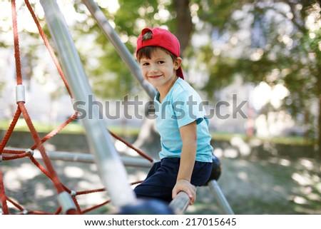 Little boy in cap sit on jungle gym, outdoor portrait - stock photo