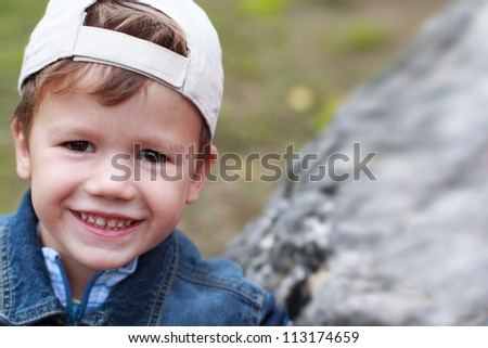 Little boy in cap smiling - stock photo