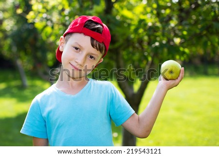 Little boy in cap with fresh apple, outdoor portrait - stock photo