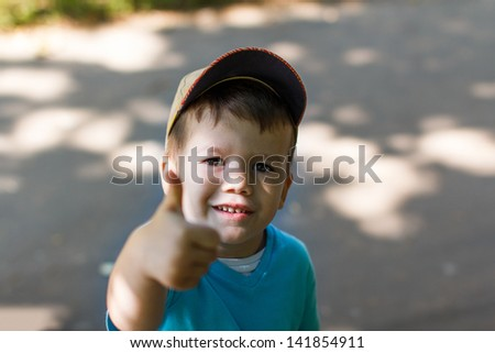 Little boy in cap with victory sign, outdoors - stock photo
