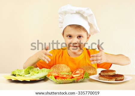 Little boy in chef hat at the table with ingredients for hamburger - stock photo