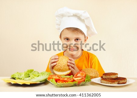Little boy in chef hat at the table with ingredients is going to cook a hamburger - stock photo