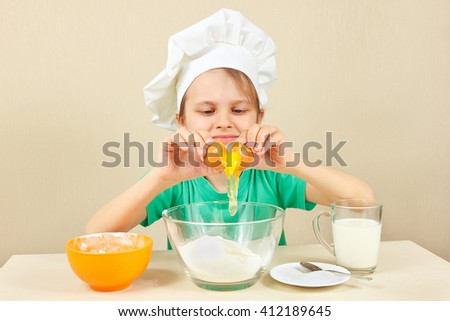 Little boy in chef hat pours egg for baking the cake - stock photo