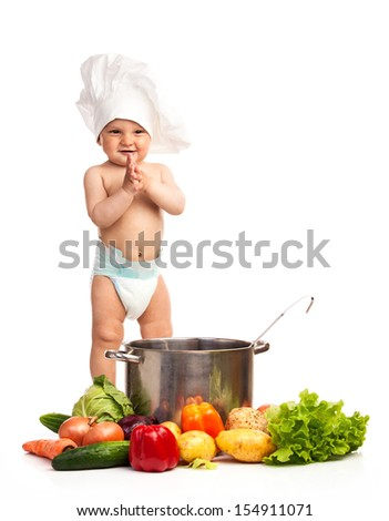 Little boy in chef's hat standing among fresh vegetables, isolated over white  - stock photo