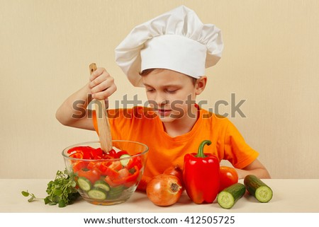 Little boy in chefs hat mixing the vegetables in a bowl with salad - stock photo