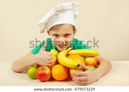Little boy in chefs hat with fruits at the table