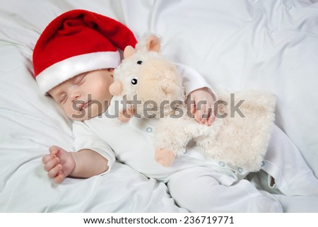 Little boy in Christmas hat asleep hugging favorite toy - stock photo