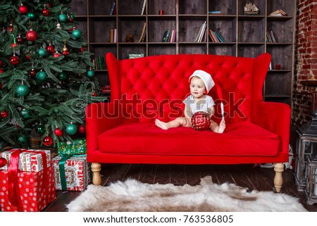 Little boy in Christmas hat sitting on sofa at Christmas, New Year