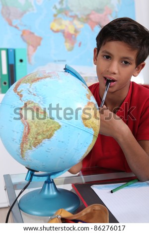 Little boy in classroom, looking bored - stock photo