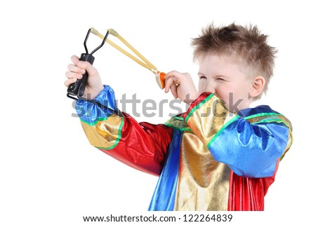Little boy in clown costume holds slingshot and aims isolated on white background.