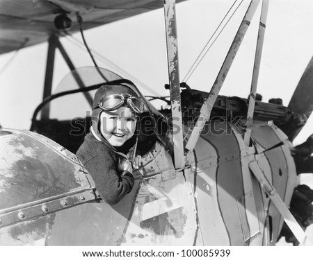 Little boy in cockpit of plane - stock photo