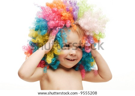 Little boy in colorful bright wig holding his head laughing - stock photo