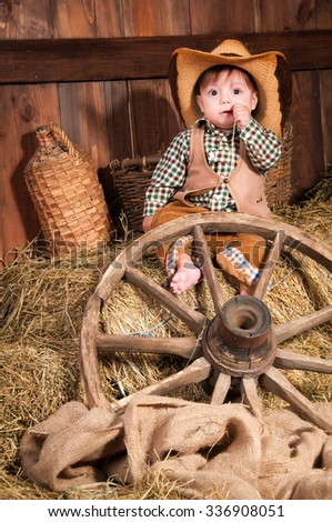 Little boy in cowboy hat, a waistcoat and a plaid shirt sitting in the hay - stock photo