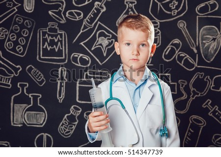 Little boy in doctor costume holding syringe on dark background with pattern.