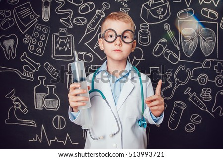 Little boy in doctor costume holding syringe on dark background with pattern. Lifts thumbs up. The child has glasses