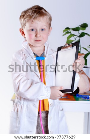 Little boy in doctor uniform and medical tools - stock photo