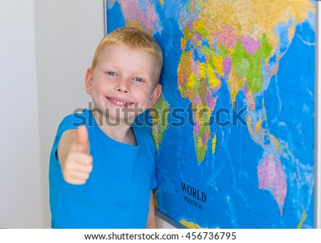 Little boy in front of American flag with thumbs up - stock photo