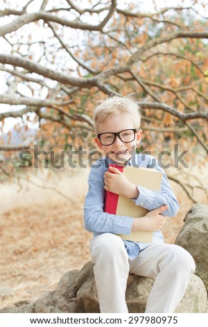little boy in glasses holding book ready for school, back to school concept - stock photo
