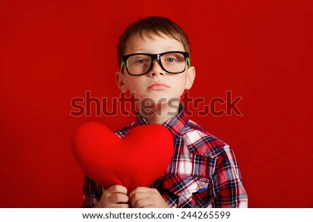 Little boy in glasses with a heart of toy in hands - stock photo