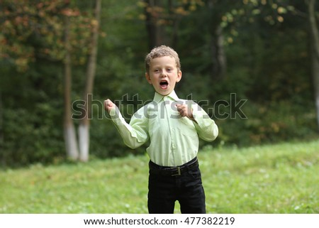 Little boy in green shirt and black trousers sings in the park