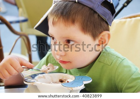 Little boy in green shirt eats ice-cream in outdoor cafe