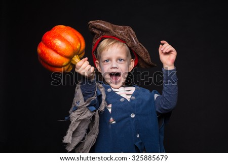 Little boy in halloween costume of pirate posing with pumpkin over black background. Studio portrait - stock photo