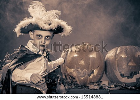 Little boy in halloween costume of pirate posing with pumpkins. Black-and-white. - stock photo
