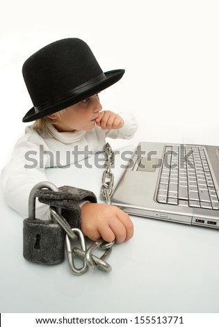 Little boy in handcuffs is studying computer - stock photo
