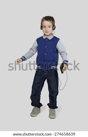 Little boy in headphones dancing with cell phone in hand on gray background - stock photo
